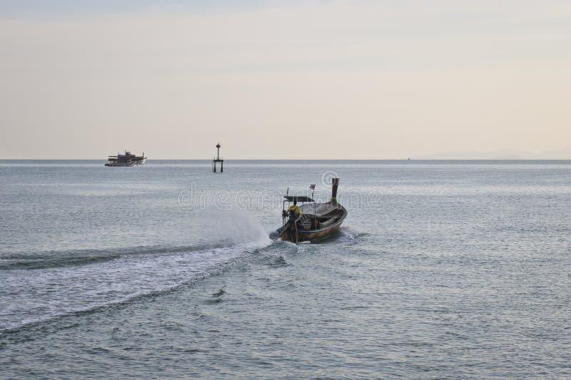 Een lege motorboot met lange staart drijft op het overzees in de avond - eind van werkdag stock afbeeldingen