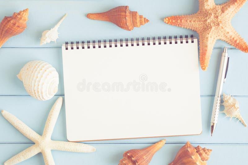 Een lege nota met zeester en overzeese shells op een blauwe houten vloer royalty-vrije stock foto