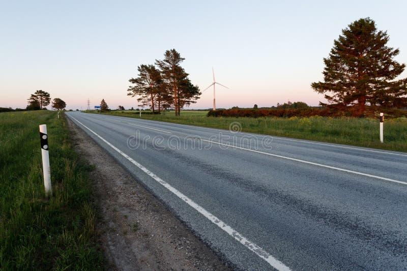 Een lege weg die een landelijk landschap onder een zonsonderganghemel doornemen met zonlicht royalty-vrije stock foto's