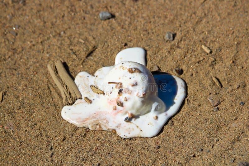 Een lepel die van roomijs in het zand op het strand smelten stock foto