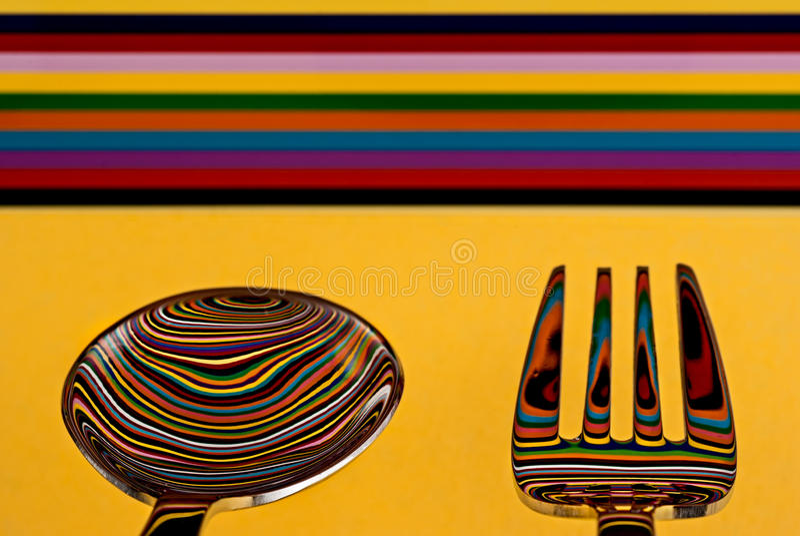 Een lepel en een vork tegen een hoogst gekleurde achtergrond, met B royalty-vrije stock fotografie