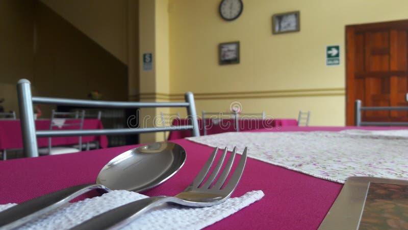 Een lepel en een vork over een eettafel stock afbeeldingen