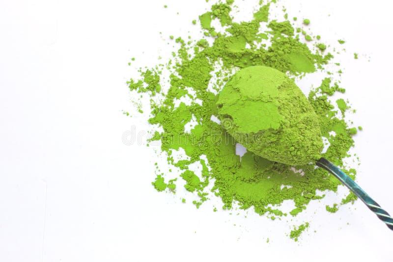 Een lepel met gepoederde matcha groene thee, die op witte achtergrond, exemplaar ruimte, hoogste mening wordt geïsoleerd stock afbeelding
