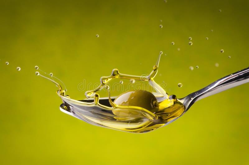 Een lepel met olie het bespatten onder een val van groene olijf royalty-vrije stock afbeelding