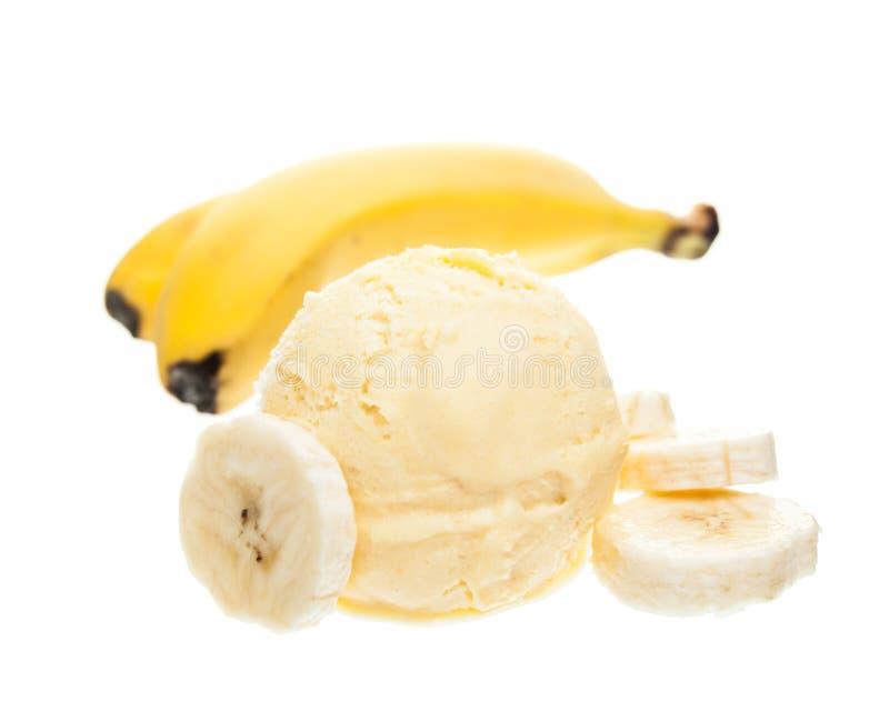 Een lepel van banaanroomijs naast een banaan op witte achtergrond wordt geïsoleerd die royalty-vrije stock foto's