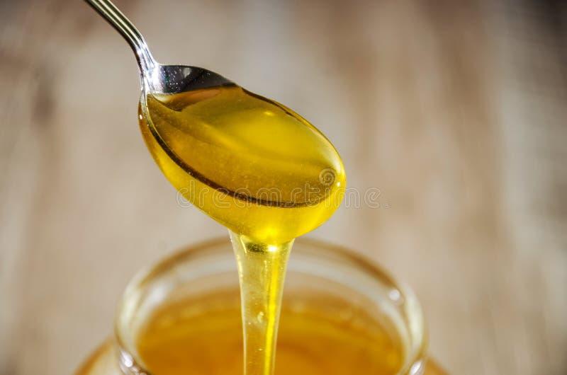 Een lepel zoete, verse honing Honing in een lepel op een kruikachtergrond Close-up Honingsstromen van een lepel in een kruik royalty-vrije stock afbeelding