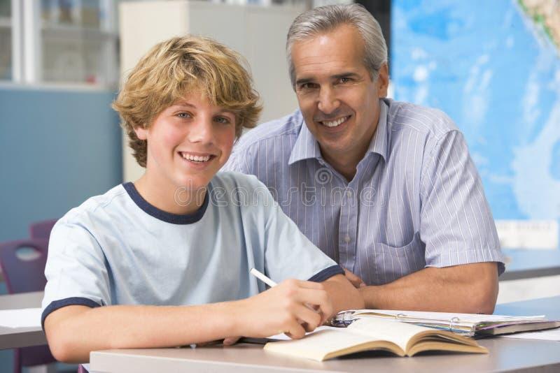Een leraar instrueert een schooljongen stock afbeelding