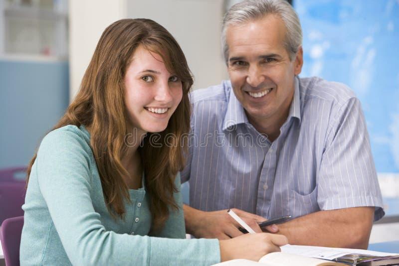 Een leraar instrueert een schoolmeisje stock foto