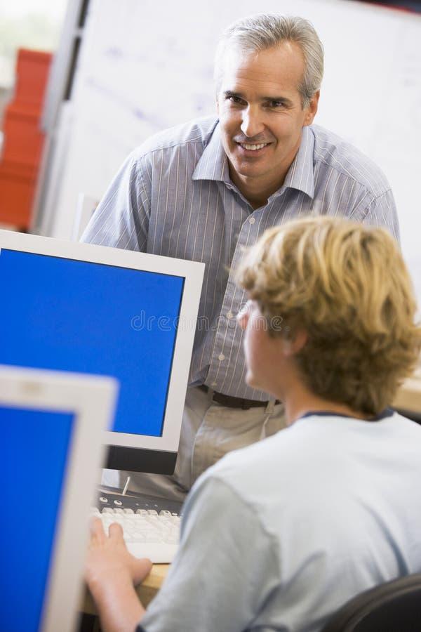 Een leraar spreekt aan een schooljongen gebruikend een computer royalty-vrije stock afbeeldingen