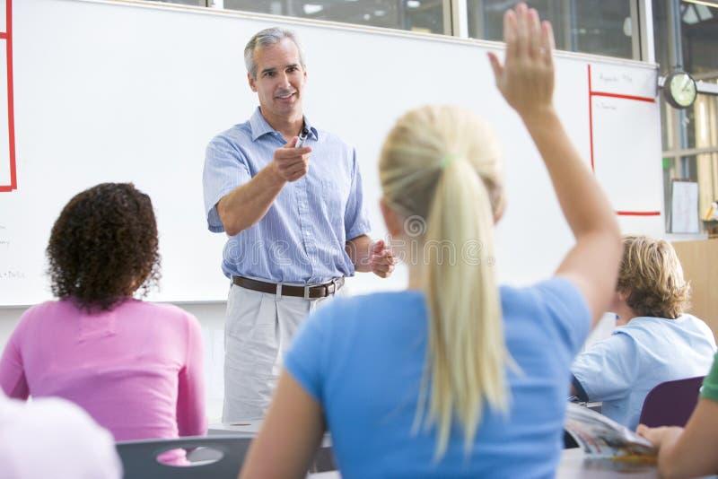 Een leraar spreekt aan schoolkinderen in een klasse stock afbeeldingen
