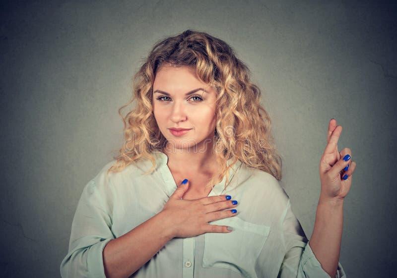 Een leugenaar jonge vrouw die een belofte maken stock afbeeldingen