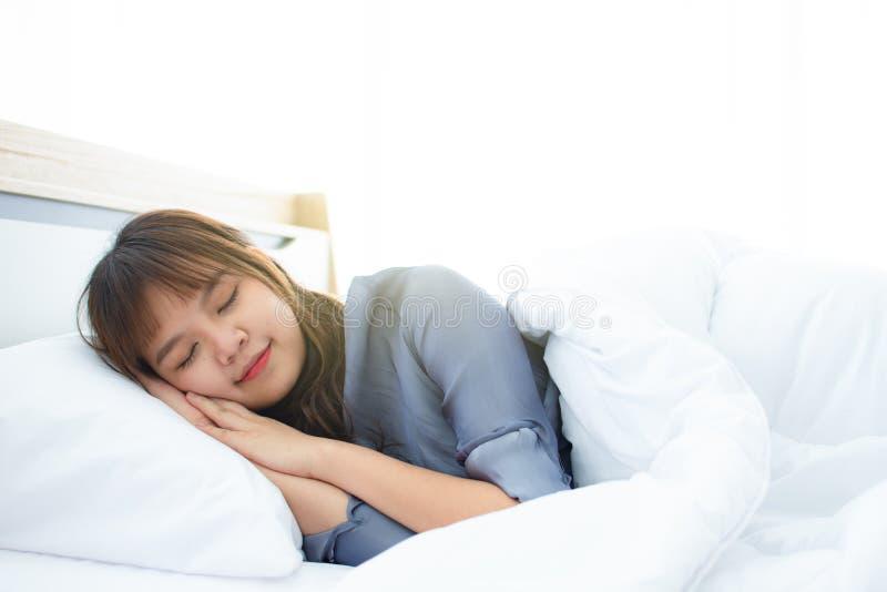 Een leuk Aziatisch meisje speeping goed op het comfortabele witte bed royalty-vrije stock fotografie