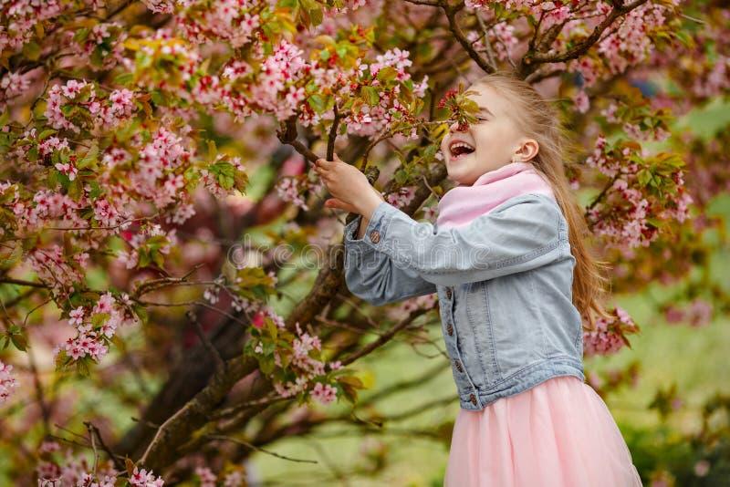 Een leuk blondemeisje glimlacht tegen een achtergrond van roze sakurabu royalty-vrije stock afbeelding