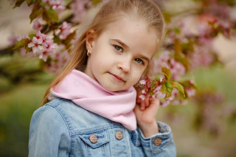 Een leuk blondemeisje glimlacht tegen een achtergrond van roze sakurabu royalty-vrije stock afbeeldingen