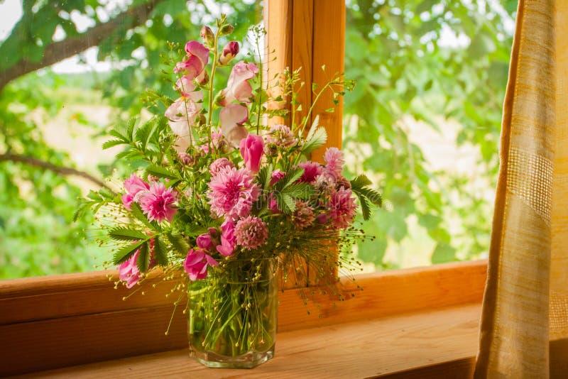 Een leuk boeket van roze korenbloemen en leeuwebek op een houten venstervensterbank stock afbeeldingen