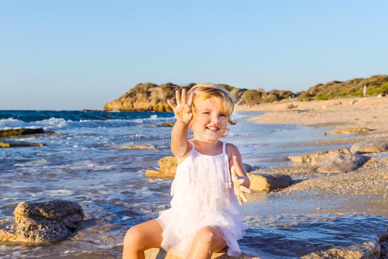 Een leuk klein aanbiddelijk peutermeisje die in witte kleren met zand en shells op het lege strand op een warme zonnige de zomerd stock fotografie