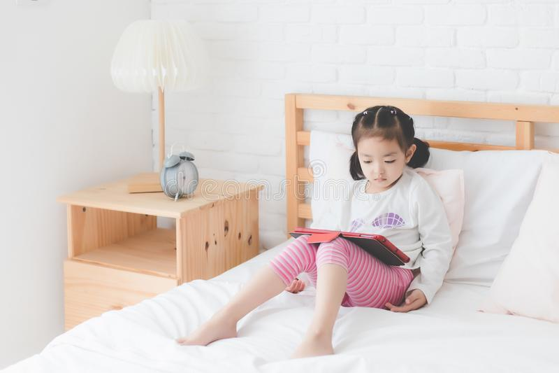 Een leuk klein Aziatisch meisje, Thaise mensen die een wit lang-sleeved overhemd dragen, zit op bed en speelt een tablet in slaap royalty-vrije stock foto's