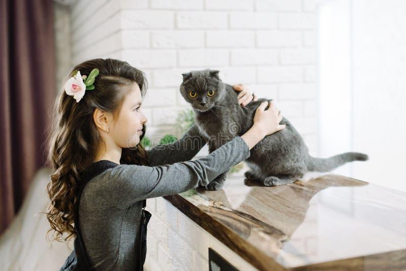 Een leuk meisje brengt haar tijd met haar zoete kat door stock afbeelding