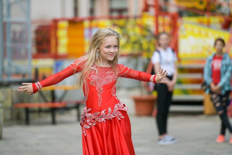 Een leuk meisje in een rood kostuum danst op de straat Meisje in de dansklasse Het babymeisje leert dans Toon dans aan stock afbeelding