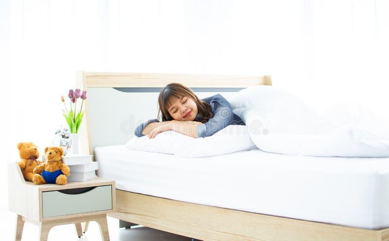 Een leuk meisje slaapt op haar bed stock afbeeldingen