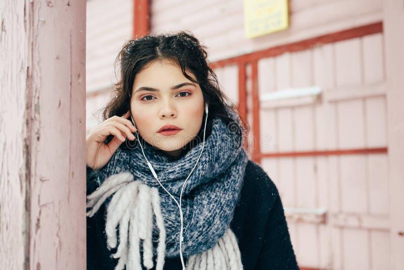 Een leuk meisje zit en luistert aan muziek in de wintertijd stock foto