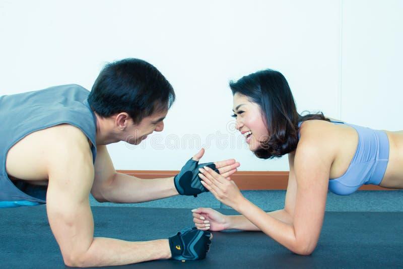 Een leuk paar met sportwears planking in gymnastiek stock afbeeldingen