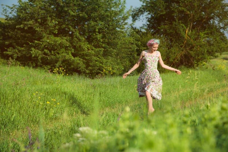 Een leuk vrolijk jong meisje in een lichte katoenen kleding wandelt langs de landweg tegen de achtergrond van de zomer stock afbeelding