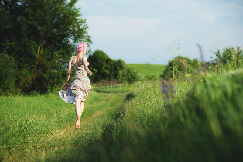 Een leuk vrolijk jong meisje in een lichte katoenen kleding wandelt langs de landweg tegen de achtergrond van de zomer royalty-vrije stock fotografie