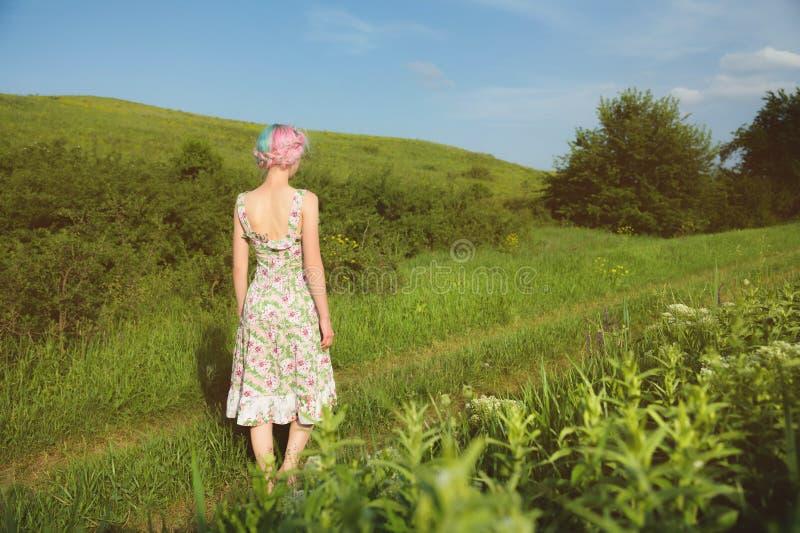 Een leuk vrolijk jong meisje in een lichte katoenen kleding wandelt langs de landweg tegen de achtergrond van de zomer stock foto's