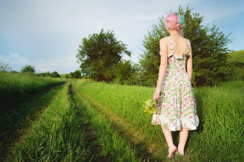 Een leuk vrolijk jong meisje in een lichte katoenen kleding wandelt langs de landweg tegen de achtergrond van de zomer stock afbeeldingen