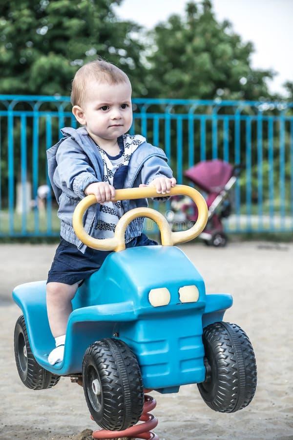 Een leuke babyjongen die een grote stuk speelgoed auto op een de zomerspeelplaats drijven stock afbeeldingen