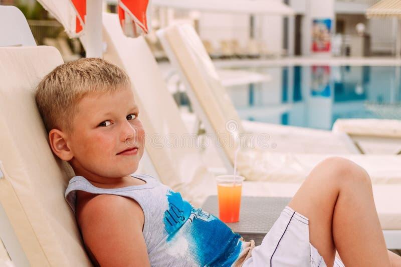 Een leuke blonde Kaukasische zeven-jaar-oude jongen ligt door de openluchtpool Oranje Fruitcocktail royalty-vrije stock afbeeldingen