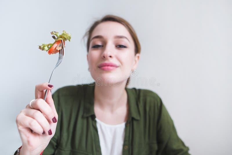 Een leuke glimlachende vrouw met een vork van salade in haar hand is geïsoleerd op een grijze achtergrond stock foto's