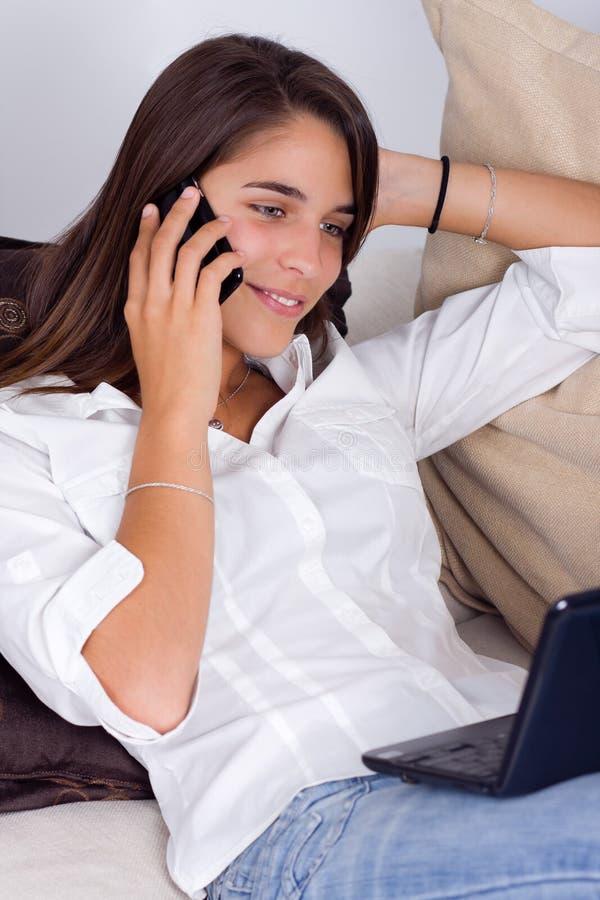 Een leuke jonge vrouw die op de telefoon spreekt stock fotografie