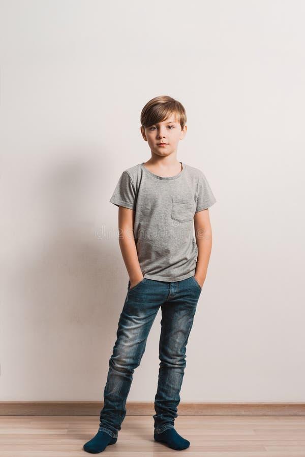 Een leuke jongen door de witte muur, grijs overhemd, blauwjeans stock fotografie
