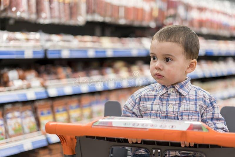 Een leuke jongen kleedde zich in een plaidoverhemd in een supermarkt in een karretje Tegen de achtergrond van planken met vleeswa royalty-vrije stock foto