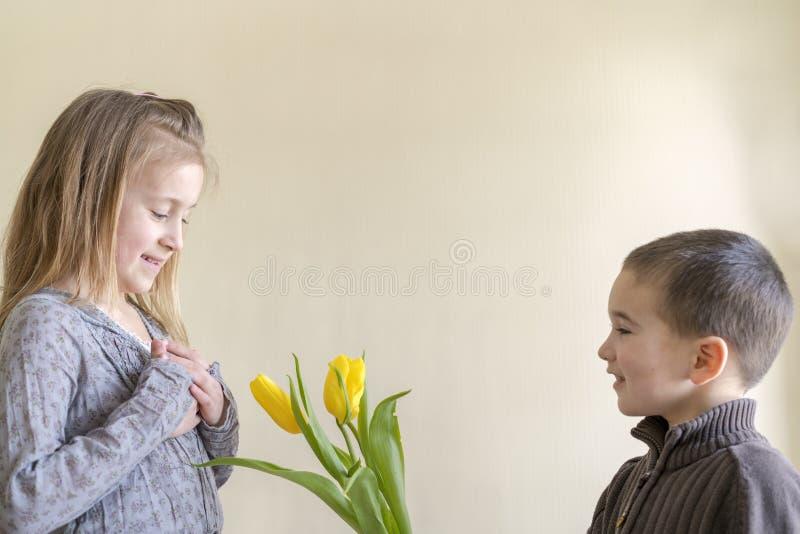 Een leuke kleine jongen geeft bloemen aan een meisje dat ouder is dan hem Het concept liefde en vriendschap stock foto