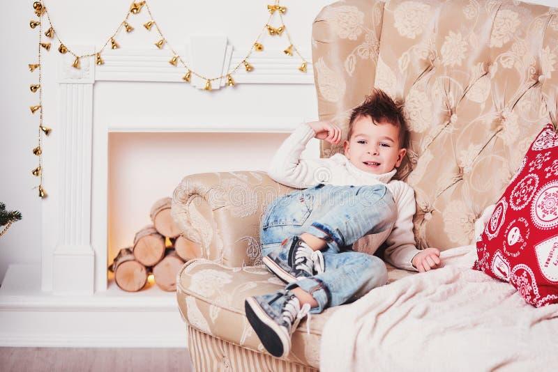 Een leuke kleine jongen lacht en ligt op de laag Een vrolijke kerel in een gebreide sweater en een modieus kapsel rust op de laag stock afbeelding
