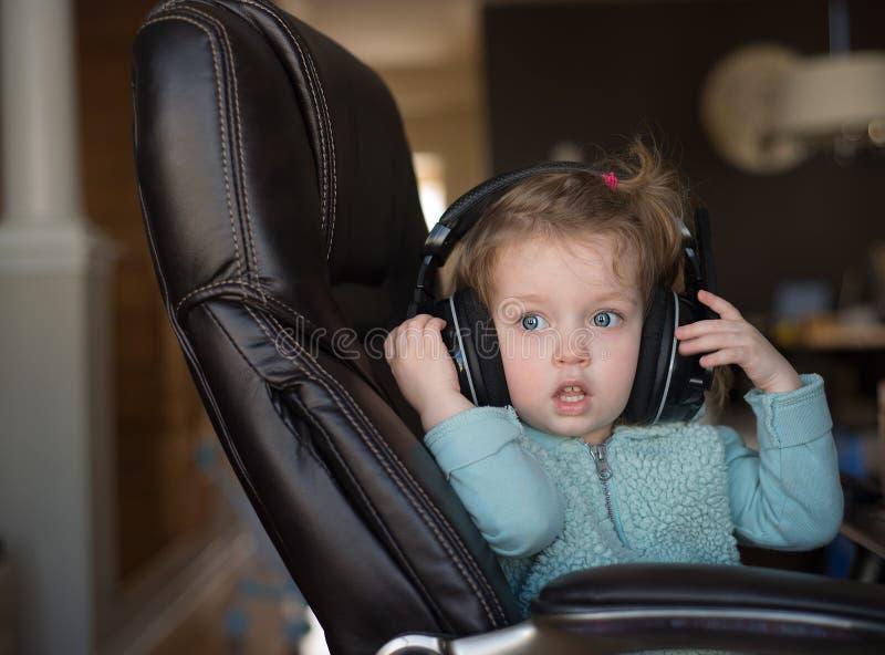 Een leuke kleine Kaukasische blondebaby met blauwe ogen met hoofdtelefoons zit op een stoel en kijkt vooruit stock fotografie