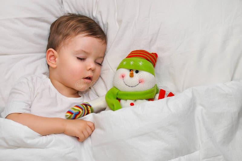 Een leuke peuterjongen slaapt op wit linnen met zijn favoriete stuk speelgoed sneeuwman royalty-vrije stock afbeelding