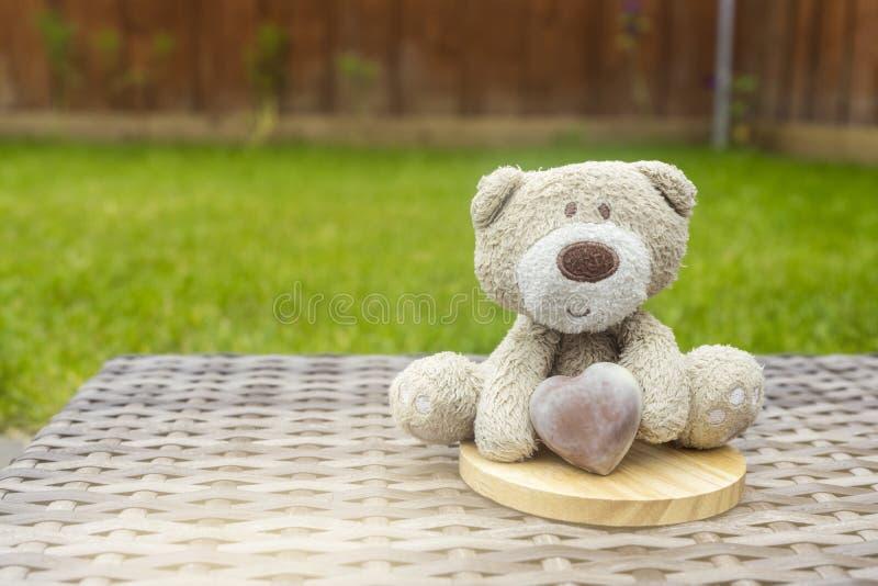 Een leuke teddybeer die de bruine zitting van het melkchocolahart op de bovenkant van ronde houten onderlegger voor glazen op pla stock foto's