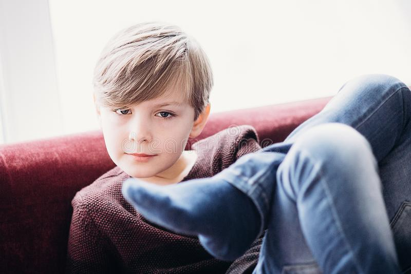 Een leuke zitting van het jongensjonge geitje op een bank, gekruiste benen royalty-vrije stock foto