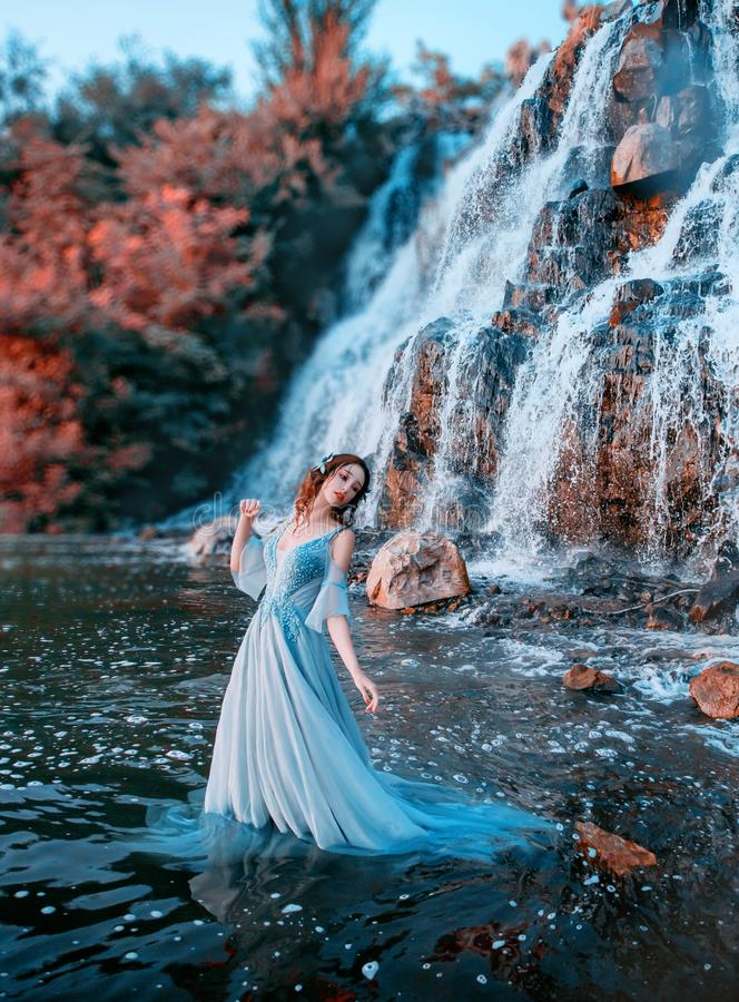 Een liefdevol meisje met een eerlijke huid staat in aqua met een lang blauw jurk stock afbeelding