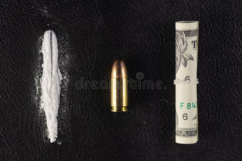 Een lijn van cocaïnepoeder, de enige kogel en de dollarrekening scrollen op zwarte oppervlakte stock afbeelding