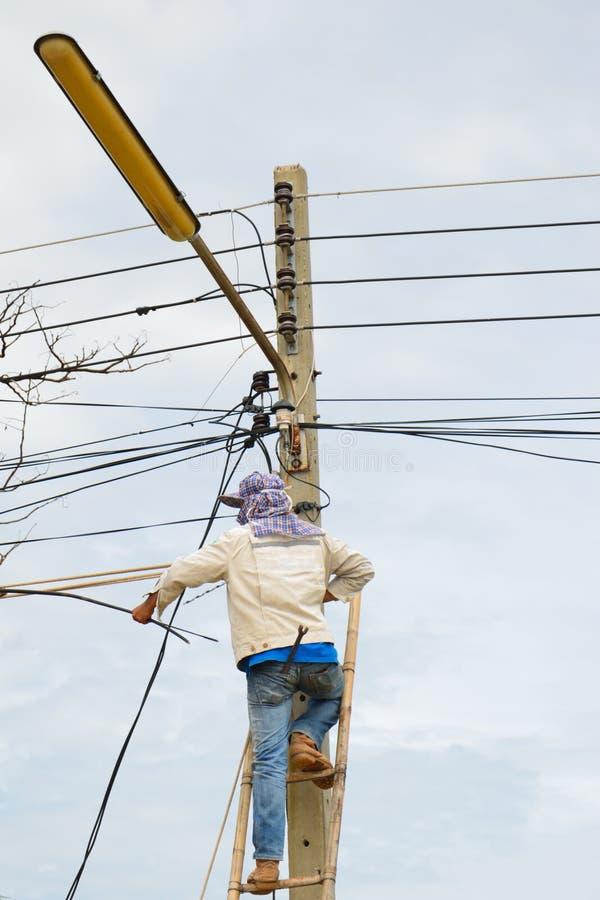 Een lijnwachter die aan kabel werkt stock foto's