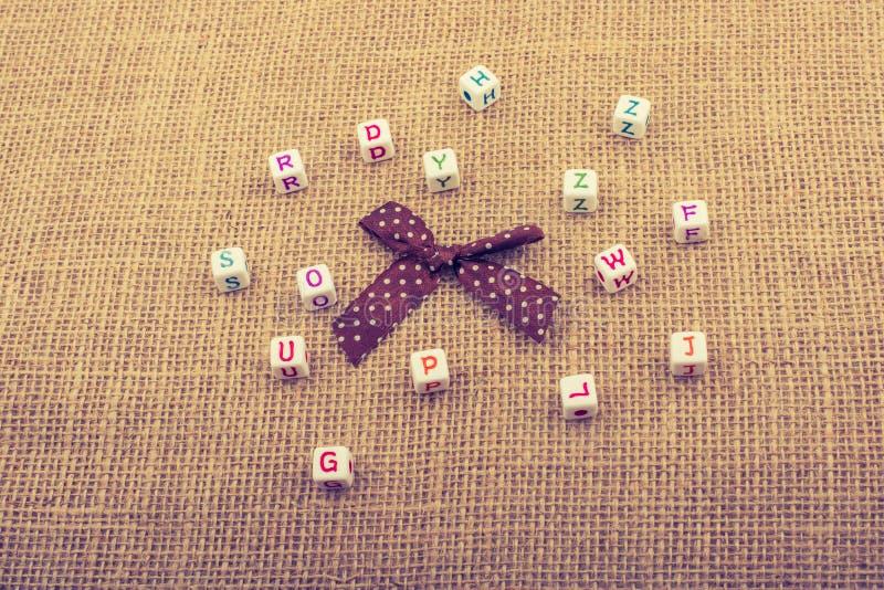 Een lint en verspreide dobbelen-gerangschikte alfabetkubussen op geweven s stock afbeelding
