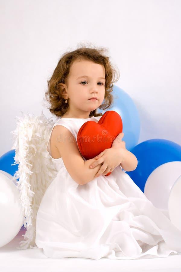 Een littlelengel met rood hart stock foto's