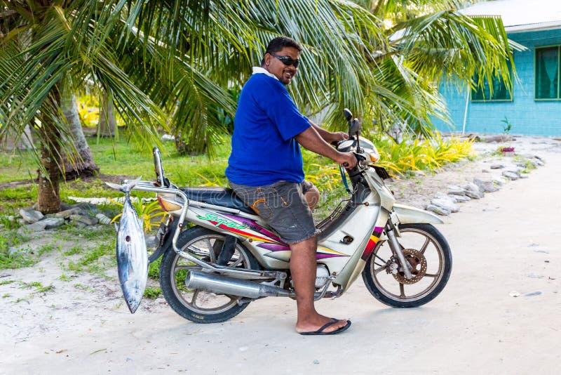 Een lokale inheemse Polynesische mens op een motorfiets met een tonijn, Tuvalu royalty-vrije stock fotografie