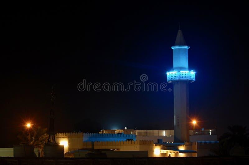 Een lokale moskee die bij nacht onder de omringende huisvesting gloeien die de vraag aan gebed in de Verenigde Arabische Emiraten royalty-vrije stock foto