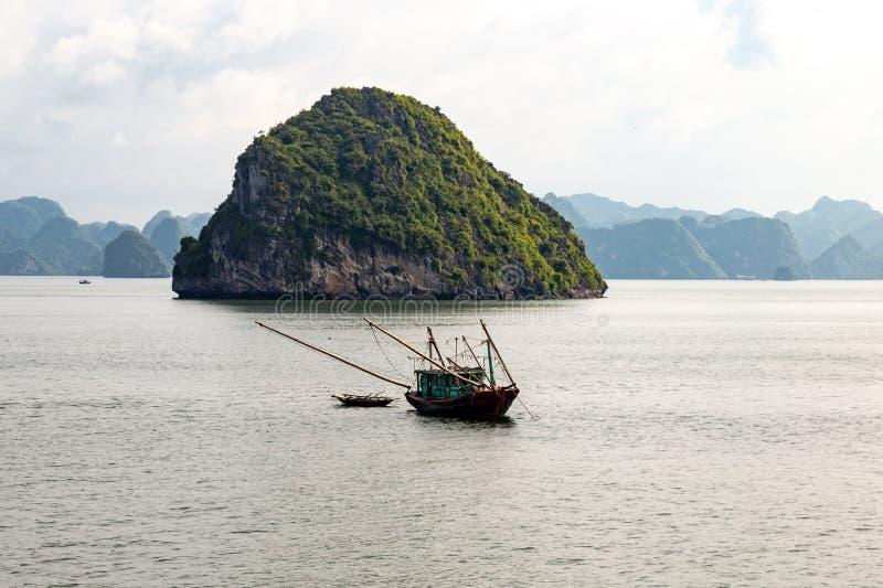 Een lokale vissersboot onder de karst vormingen in Halong-Baai, Vietnam, in de golf van Tonkin royalty-vrije stock fotografie